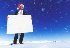 Conceito de Holding Blank Placard do homem de negócios do Natal foto de stock