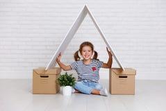 Conceito de mover-se e do abrigar menina feliz da criança com caixas imagem de stock royalty free