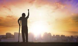 Conceito de Paralympic: pessoa deficiente com a silhueta das muletas no fundo do por do sol, no dia internacional dos enfermos ou fotos de stock