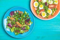 Conceito de placas deliciosas saudáveis das saladas, as alaranjadas e as azuis, tabela de madeira escura imagens de stock
