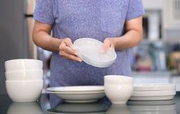 Conceito de produto da limpeza da mulher que limpa o líquido de limpeza do dishware na casa a imagem de stock royalty free