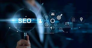 Conceito de SEO Search Engine Optimization Marketing Homem de neg?cios com a lupa ? disposi??o que procura no Web site e na rede foto de stock