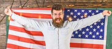 Conceito de sistema educativo americano Programa da troca do estudante O homem com barba e bigode na cara feliz guarda a bandeira imagem de stock