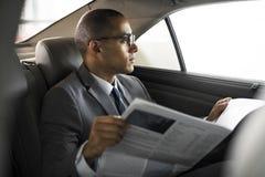 Conceito de Sit Read Newspaper Inside Car do homem de negócios foto de stock