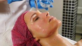 Conceito de Skincare Mulher nova no sal?o de beleza de beleza M?scara facial de Applying do esteticista ao cliente f?mea Termas R vídeos de arquivo