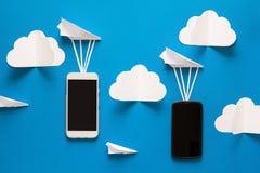 Conceito de transferência de dados Passagem da mensagem Dois smartphones móveis e aviões de papel imagem de stock royalty free