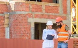 Conceito de uma comunicação da equipe da construção O coordenador e o construtor da mulher comunicam o canteiro de obras Discuta  fotos de stock royalty free