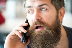 Conceito de uma comunicação Homem com fundo defocused da conversação de telefone celular da barba e do bigode Posse farpada do ho foto de stock
