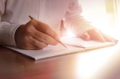 Conceito de uma escrita do homem de negócios em um caderno Foto de Stock Royalty Free