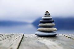 Conceito de Zen Balancing Pebbles Misty Lake imagem de stock