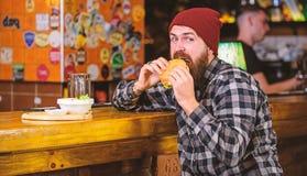 Conceito delicioso do hamburguer Aprecie o gosto do hamburguer fresco O homem com fome do moderno come o hamburguer O homem com b imagem de stock
