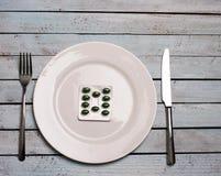 Conceito do abuso da dieta ou da medicina - comprimidos verdes na placa com knif foto de stock