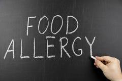 Conceito do alimento da alergia Mão com o giz que escreve no quadro preto fotografia de stock