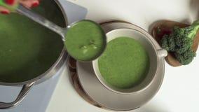 Conceito do alimento, o culinário e o saudável comer - fim acima da sopa verde vegetal do creme do romanesco na bacia com rúcula  vídeos de arquivo