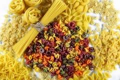 Conceito do alimento - vária massa italiana cru, crua no fundo branco, vista superior, grupo Fotografia de Stock