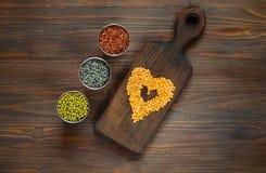 Conceito do alimento do vegetariano Cereais e feijões para cozinhar em um fundo de madeira escuro imagem de stock