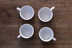 Conceito do alimento - vista superior de quatro copos brancos sem os pires na tabela de madeira marrom cinzenta Canecas cerâmicas Fotos de Stock Royalty Free