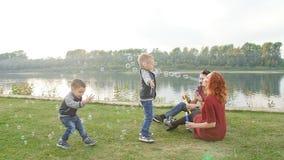 Conceito do amor e da paternidade A família feliz com crianças funde bolhas de sabão fora filme