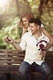 Conceito do amor e do casamento Pares felizes novos que sentam-se no parque Imagens de Stock