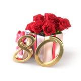 Conceito do aniversário com as rosas vermelhas no presente isolado no fundo branco eightieth 80th 3d rendem Foto de Stock