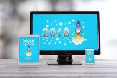 Conceito 2018 do ano novo em dispositivos diferentes Fotografia de Stock Royalty Free
