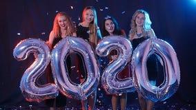 Conceito do ano novo feliz O grupo de jovens mulheres está tendo o divertimento e está guardando uns números mais grandes 2020 video estoque