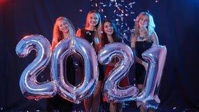 Conceito do ano novo feliz O grupo de jovens mulheres está tendo o divertimento e está guardando uns números mais grandes 2021 filme