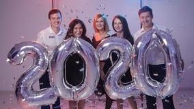 Conceito 2020 do ano novo Grupo de jovens alegres que guardam balões do número, regado com os confetes vídeos de arquivo