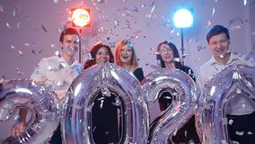 Conceito 2020 do ano novo Grupo de jovens alegres que guardam balões do número, regado com os confetes filme