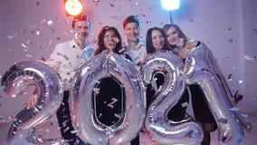 Conceito 2021 do ano novo Grupo de jovens alegres que guardam balões do número, regado com os confetes vídeos de arquivo