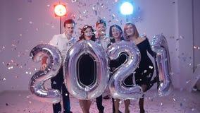 Conceito 2021 do ano novo Grupo de jovens alegres que guardam balões do número, regado com os confetes video estoque