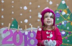 Conceito 2018 do ano novo Menina pequena bonita que decora o numeral do ano novo fundo de uma árvore de Natal pintada e Fotografia de Stock Royalty Free