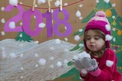 Conceito 2018 do ano novo Menina pequena bonita que decora o numeral do ano novo fundo de uma árvore de Natal pintada e Imagens de Stock