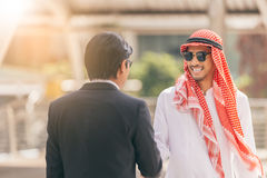 Conceito do aperto de mão Negócio árabe e homem de negócios que agitam as mãos imagens de stock royalty free