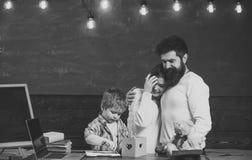 Conceito do apoio do pai Pais que olham seu desenho do filho, aprendendo escrever, quadro no fundo Menino em ocupado foto de stock