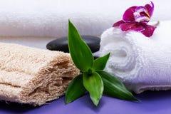 Conceito do bem-estar dos termas Esponja natural da bucha, rolada acima das toalhas brancas, das pedras empilhadas do basalto, do fotografia de stock