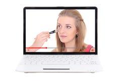 Conceito do blogue da beleza - a aplicação bonita da menina compõe no portátil foto de stock