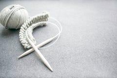 Conceito do bordado: agulhas de confecção de malhas, fio de algodão amarrado cinzento, s foto de stock