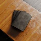 Conceito do caderno três vazio com tampa de papel textured preta na mesa de madeira Modelo horizontal vazio Vista superior 3d Imagem de Stock
