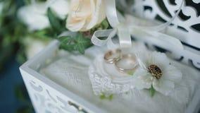 Conceito do casamento Alianças de casamento em uma caixa de madeira feito a mão, cercado por flores em um fundo de turquesa video estoque