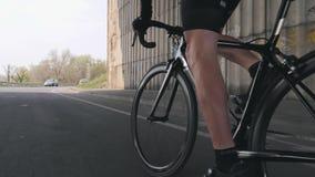 Conceito do ciclismo Bicicleta pedaling dos músculos fortes do pé Bicicleta da equitação do ciclista fora da sela Perto siga acim filme