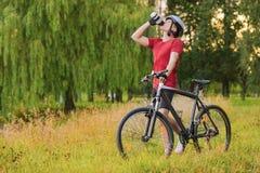 Conceito do ciclismo: Ciclista masculino caucasiano novo que tem a ruptura da água imagens de stock