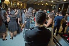 Conceito do concerto da vida noturno O DJ está para trás à câmera na frente da multidão de senhoras e considerável equipa a dança fotografia de stock royalty free