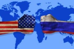 Conceito do conflito dos governos Punhos masculinos coloridos nos EUA e nas bandeiras do russo no fundo do mapa do mundo Conflito fotografia de stock