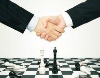 Conceito do consenso com os homens que agitam as mãos e os penhores da xadrez fotos de stock royalty free