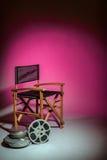 A cadeira do director de cinema com carretel do filme Fotografia de Stock