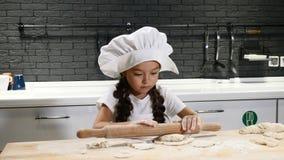 Conceito do cozinheiro chefe da criança Menina bonita pequena no avental do chapéu do cozinheiro chefe e do cozinheiro chefe que  vídeos de arquivo
