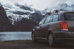 conceito do curso Carro no fundo de montanhas e de lagos neve-tampados Tiro da parte traseira Pode usar-se como a bandeira fotos de stock