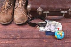 Conceito do curso com mala de viagem do vintage, óculos de sol, a câmera velha, as botas da camurça, a caixa para o dinheiro e o  Imagens de Stock Royalty Free