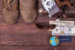 Conceito do curso com mala de viagem do vintage, óculos de sol, a câmera velha, as botas da camurça, a caixa para o dinheiro e o  Foto de Stock